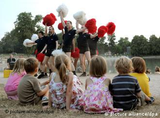 Gay Games cheerleaders practice in front of a group of children