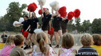 Gay Games cheerleaders practice in front of a group of children