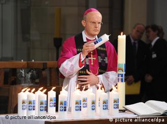 Bishop Overbeck lights candles at the Duisburg memorial service