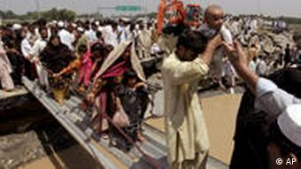 People walk over a makeshift bridge to dryer ground