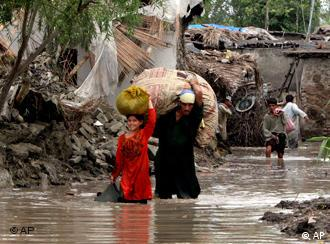 Local residents transport their belonging through a street flooded by heavy monsoon rains