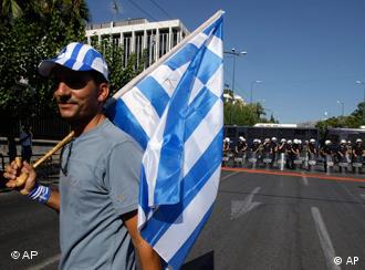 A protesting trucker stands in the middle of a road holding a Greek flag