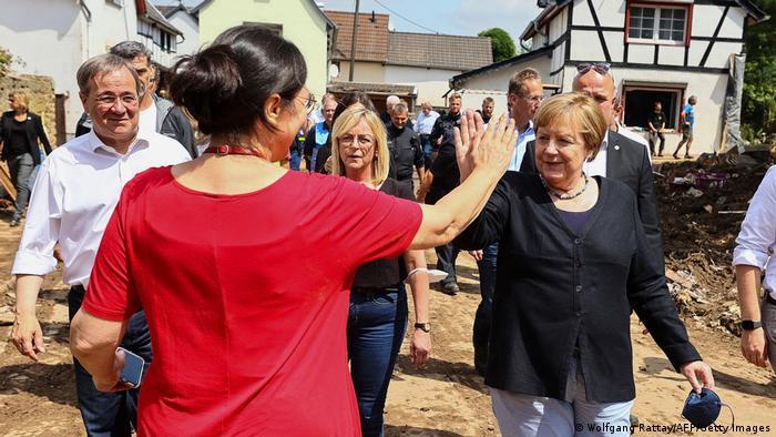 German Chancellor Angela Merkel high-fives resident Martha Mueller-Heinen during a visit to the flood-ravaged city of Iversheim, near Bad Munstereifel, North Rhine-Westphalia state