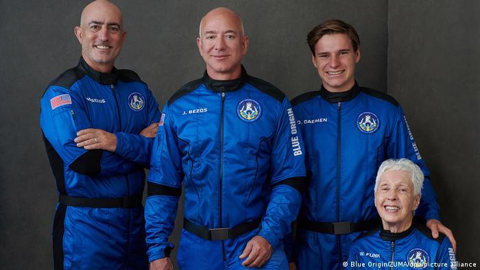 در این سفر والی فانک۸۲ ساله (نشسته در عکس) به عنوان مسنترین فضانورد، اولیور دیمن ۱۸ ساله (از سمت راست نفر اول ایستاده) به عنوان جوانترین مسافر و مارک بزوس (نفر اول سمت چپ) برادر جف بزوس نیز حضور داشتند.