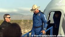This photo provided by Blue Origin, Jeff Bezos, founder of Amazon and space tourism company Blue Origin, exits the Blue Origin's New Shepard capsule after it parachuted safely down to the launch area with passengers Mark Bezos, Oliver Daemen and Wally Funk, near Van Horn, Texas, Tuesday, July 20, 2021. (Blue Origin via AP)