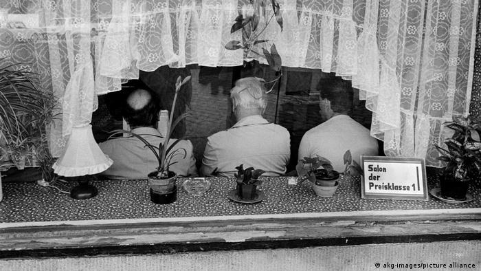 Tres hombres sentados en una peluquería de Alemania Oriental.