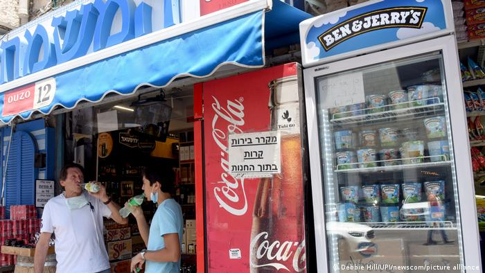 A Ben & Jerry's fridge full of ice cream in a shop. There are signs in Hebrew. Two men are stood inside the shop drinking from bottles.