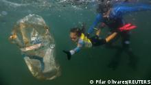 4-year-old Nina Gomes, who was named as the youngest Green Agent by the Municipal Urban Cleaning Company (COMLURB), collects garbage in the sea accompanied by her father Ricardo Gomes, marine biologist and director of the NGO Instituto Mar Urbano, at the Praia Vermelha beach in Rio de Janeiro, Brazil July 9, 2021. Picture taken July 9, 2021. REUTERS/Pilar Olivares TPX IMAGES OF THE DAY