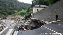 A policeman looks at a piece of road that has sunken in the city of Altenahr, Rhineland-Palatinate, western Germany, on July 19, 2021, after devastating floods hit the region. - The German government on July 19, 2021 pledged to improve the country's under-fire warning systems as emergency services continued to search for victims of the worst flooding in living memory, with at least 165 people confirmed dead. (Photo by CHRISTOF STACHE / AFP)