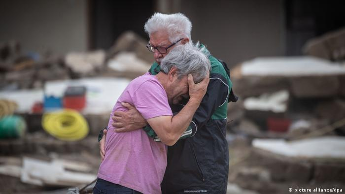 Two brothers embrace after having lost their family home in Altenahr, Germany, after catastrophic flooding in July 2021