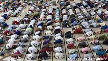 People offer prayers to mark the start of the Muslim festival Eid al-Adha or the 'Festival of Sacrifice, in Dhaka on July 21, 2021. (Photo by Munir Uz zaman / AFP)