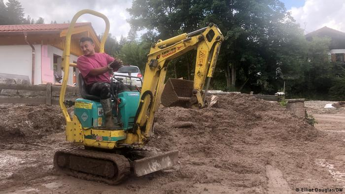 Local Josef Wanker clears land after flooding with the help of a digger
