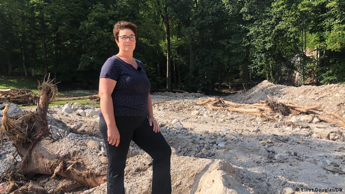 Eine Frau mit kurzen Haaren und Brille steht am Hang vor einer Fläche voller Sand, Geröll und Baumstämmen