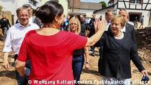 20.07.2021 Bundeskanzlerin Angela Merkel (CDU, r) und Anwohnerin Martha Mueller-Heinen klatschen sich ab. Merkel und Armin Laschet (CDU, l), Ministerpräsident von Nordrhein-Westfalen, informieren sich über die Lage im vom Hochwasser betroffenen Stadtteil Iversheim und treffen Opfer der Flutkatastrophe.