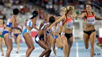 Germany's Janin Lindenberg, right, passes the baton to Claudia Hoffmann, second from right