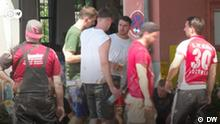 DW Reportage Videostill l Erftstadt, Helfer mit 1. FC Koeln Trikot https://www.dw.com/en/volunteers-join-cleanup-after-severe-floods-in-germany/av-58310027