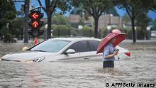 TOPSHOT - This photo taken on July 20, 2021 shows a man wading past a submerged car along a flooded street following heavy rains in Zhengzhou in China's central Henan province. - - China OUT (Photo by STR / AFP) / China OUT (Photo by STR/AFP via Getty Images)