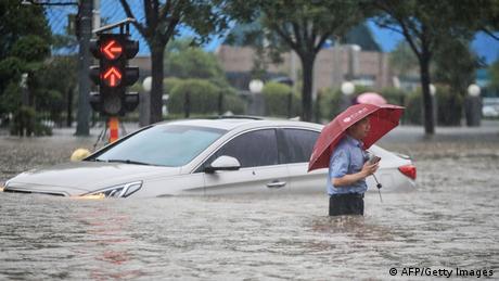 Ein Mann mit Regenschirm steht bis zur Hüfte in den Fluten. Im Hintergrund ein Auto, das in den Fluten feststeckt