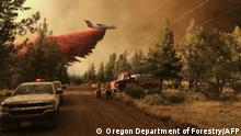 This photo provided by the Oregon Department of Forestry shows a firefighting tanker droping a retardant over the Grandview fire near Sisters, Oregon on July 11, 2021. (Photo by Handout / Oregon Department of Forestry / AFP) / RESTRICTED TO EDITORIAL USE - MANDATORY CREDIT AFP PHOTO /Oregon Department of Forestry - NO MARKETING - NO ADVERTISING CAMPAIGNS - DISTRIBUTED AS A SERVICE TO CLIENTS