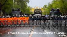 Scores of police officers, around half wearing orange, are standing behind a barrier and barbed wire in the middle of a street. Behind them are two water trucks and a truck with loudspeakers. In the background is an ornamental arch.