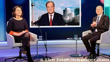 Unions-Kanzlerkandidat Armin Laschet wird auf einem Fernsehschirm gezeigt, während die Mitbewerbern von Grünen und SPD, Annalena Baerbock und Olaf Scholz im Fernsehstudio bei einer Diskussionsrunde des WDR-Europaforums in Berlin sitzen. Es war das erste Aufeinandertreffen der drei Kanzlerkandidaten - wobei nur Baerbock und Scholz mit der Moderatorin im Studio saßen, Laschet war zugeschaltet. +++ dpa-Bildfunk +++