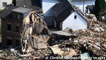 A person walks past destroyed houses in Altenburg, district of Altenahr, Rhineland-Palatinate, western Germany, on July 20, 2021, during clearing work after devastating rains and floods hit the region. (Photo by Christof STACHE / AFP) (Photo by CHRISTOF STACHE/AFP via Getty Images)
