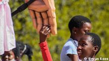 *** Bitte nur in Zusammenhang mit der Berichterstattung verwenden *** Ein Kind in rotem Oberteil nimmt die überlebensgroße Hand der Puppe Little Amal. Little Amal wird in verschiedenen Städten und Orten Halt machen und dort mit Bewohnern und Gästen interagieren. Copyright: (c) Bevan Roos