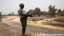25/04/2017 12:57:17 A Nigerian soldier, with a grenade launcher, stands guard near the Yobe river, that separates Nigeria from Niger, on the outskirt of the town of Damasak in North East Nigeria on April, 25 2017 as thousands of Nigerians, who were freed in 2016 by the Nigerian army from Boko Haram insurgents, are returning to their homes in Damasak. - Yagana Bukar's younger brothers Mohammed and Sadiq were among about 300 children kidnapped by Boko Haram from the town of Damasak in remote northeastern Nigeria nearly three years ago. But instead of the global outrage and social media campaign that followed a similar abduction of 219 schoolgirls from the town of Chibok, there were no protests for the children of Damasak. (Photo by Florian PLAUCHEUR / AFP)