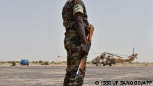 16/06/2016 09:25:42 A Niger army soldier stands guard next to a Niger's Air Force Mi-35P attack helicopter on the tarmac in Diffa, southeastern Niger, during a visit of Niger's Interior Minister on June 16, 2016 following attacks by Nigeria-based Boko Haram fighters in the region. - Interior minister Mohamed Bazoum was paying a visit in Diffa today, after Boko Haram fighters on June 9 attacked a military post in Bosso in Niger's Diffa region, killing 26 soldiers including two from neighbouring Nigeria, in one of its deadliest attacks in Niger. (Photo by ISSOUF SANOGO / AFP)