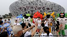 Visitors pose for photos next to 2008 Beijing Olympic mascots in front of the National Stadium also known as the Bird's Nest in Beijing on August 8, 2008 hours before the 2008 Beijing Olympic Games Opening Ceremony. Beijingers were forced to put their lives on hold August 8 as many businesses shut down and gyms, stores and cinemas were told to close early for security reasons ahead of the Olympic opening ceremony AFP PHOTO / KAZUHIRO NOGI (Photo credit should read KAZUHIRO NOGI/AFP via Getty Images)