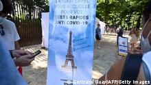 Vistors holding mobile phones stand near a Covid-19 antigenic tests area, as a banner reads 'The Eiffel Tower welcomes you for your anti Covid-19 quick tests', near The Eiffel Tower in Paris, on July 21, 2021. - People wanting to go to cinemas, museums, sporting matches and other cultural venues in France will have to show proof of Covid-19 vaccination or a negative test starting on July 21, as the country braces for a feared spike in cases from the highly transmissible Delta variant. (Photo by BERTRAND GUAY / AFP) (Photo by BERTRAND GUAY/AFP via Getty Images)