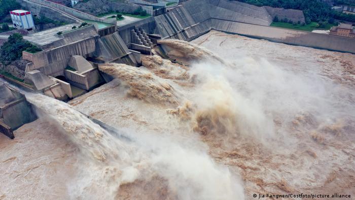 Überlauf des Wasserkraftwerks der Xiaolandi-Talsperre. Riesige braune Wassermassen strömen aus vier Kanälen sprudelnd heraus.