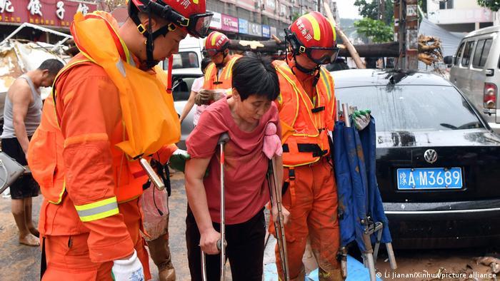Rescuers help an elderly woman in Gongyi city in Henan province.