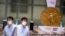 A man walks near a large-scale reproduction of the Tokyo 2020 Olympic Games gold medal as part of the Olympic Agora event at Mitsui Tower in Tokyo on July 14, 2021. (Photo by Philip FONG / AFP) (Photo by PHILIP FONG/AFP via Getty Images)