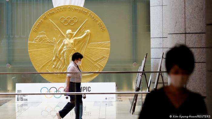 Mulher caminha diante de medalha olímpica gigante no Tóquio 2020