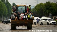TOPSHOT - People ride on a bulldozer following a heavy rain in Zhengzhou, in China's Henan province on July 22, 2021. (Photo by Noel Celis / AFP) (Photo by NOEL CELIS/AFP via Getty Images)