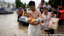 A man holding a baby wades through a flooded road following heavy rainfall in Zhengzhou, Henan province, China July 22, 2021. REUTERS/Aly Song