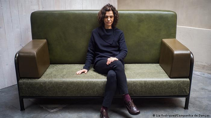 Lia Rodrigues sitzt auf grünem Sofa