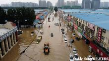 An aerial view shows rescue workers evacuating residents on a flooded road following heavy rainfall in Zhengzhou, Henan province, China July 22, 2021. Picture taken with a drone. REUTERS/Aly Song