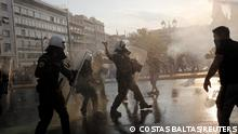 A police officer throws a tear gas canister during a protest against coronavirus disease (COVID-19) vaccinations outside the parliament building, in Athens, Greece, July 21, 2021. REUTERS/Costas Baltas