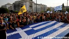 Demonstrators hold a Greek flag during a protest againstcoronavirusdisease (COVID-19) vaccinations outside the parliament building, in Athens, Greece, July 21, 2021. REUTERS/Costas Baltas