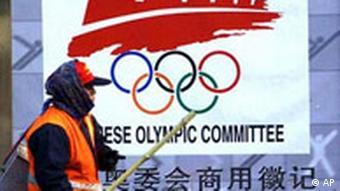 Ein Straßenkehrer vor dem offiziellen Olympiade Logo in Peking