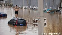 A man stands on a stranded vehicle on a flooded road following heavy rainfall in Zhengzhou, Henan province, China July 22, 2021. REUTERS/Aly Song