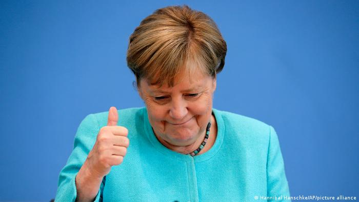 A picture of Angela Merkel wearing blue giving the thumbs up sign with her right hand.