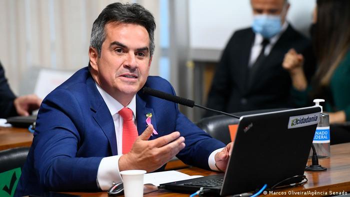 Foto mostra Ciro Nogueira, de terno azul, camisa branca e gravata vermelha, sentado em uma mesa, em frente a um notebook. Ele fala em um microfone.
