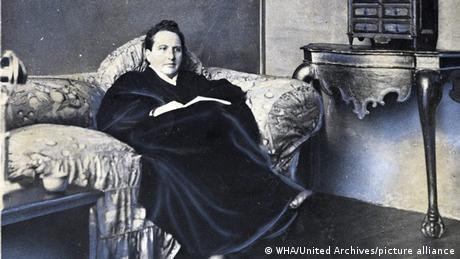 Gertrude Stein sitzt auf einem Sessel, ein Buch aufgeschlagen auf ihrem Schoß.