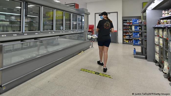 A shopper walks past an empty fridge in a London supermarket