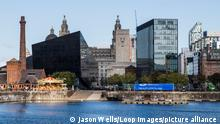 The bright sunlight reflects off the modern buildings on the Liverpool waterfront.