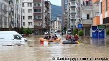 ARTVIN, TURKEY - JULY 22: People trapped in buildings are rescued with a boat on a submerged street after a stream overflowed due to heavy rains in Arhavi district of Artvin, Turkey on July 22, 2021. Gazi Nogay / Anadolu Agency