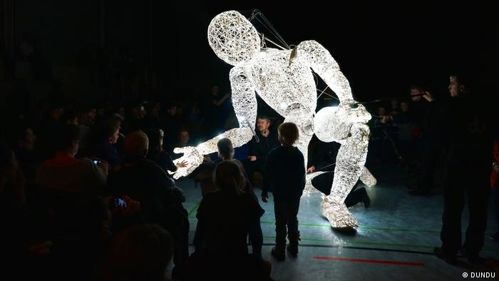 A large illuminated white puppet in a street art performance.